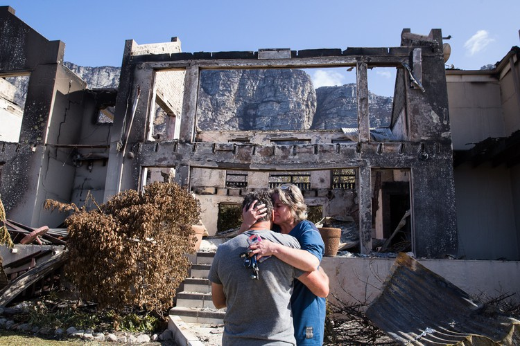 "Juanita Booyse and her husband Manie break down in tears outside their destroyed home in Bettysbay. The Booyses have been staying in Bettysbay for 9 years years and the lost of their home is ""tragic""."