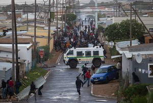 Photo of protesters running from a Nyala in Zwelihle in Hermanus.