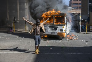 Photo of man standing in front of burning bus