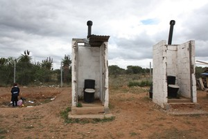 Photo of two open toilets in a field