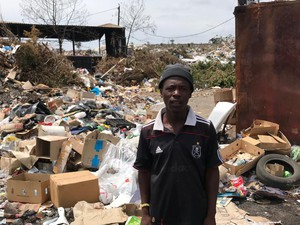Photo of man standing next to rubbish dump
