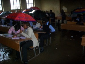 Photo of students holding umbrellas above their heads in a classroom