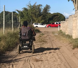 Photo of a person in a wheelchair on a dirt road