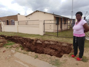 Photo of Eunice Dama pointing out the large trench in front of her yard