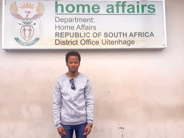 Photo of a man infront of a Home Affairs sign
