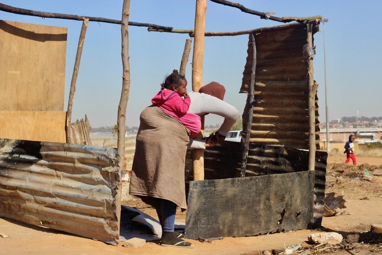 Photo of a woman with a baby on her back erecting a shack