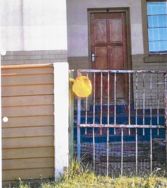 "A house with a yellow ""flag"" put up to indicate the residents need food assistance. Photo taken from court application by Cradle of Hope."