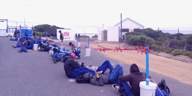 Photo of workers in uniform lying on the pavement outside gates of I&J