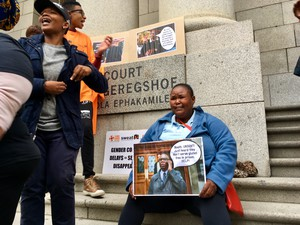 Photo of woman with poster outside court
