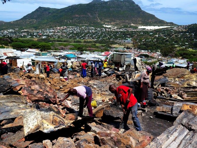 Photo of people cleaning up after fire in Imizamo Yethu.