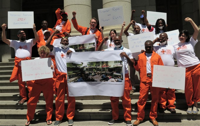 Photo of protesters in orange overalls