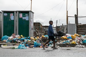 A youth walks pass rubbish in Sheffield road in Philippi East