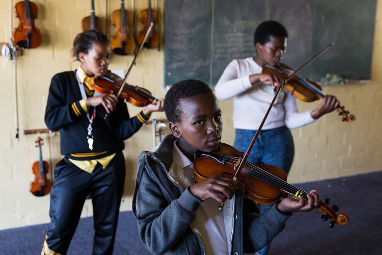 Photo of students learning violin at an outreach program in Masiphumelele