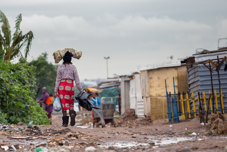 Photo of a woman walking in an informal settlement