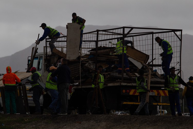 Building materials from demolished shacks owned by illegal occupiers are taken away in trucks in Parkwood. - Ashraf Hendricks