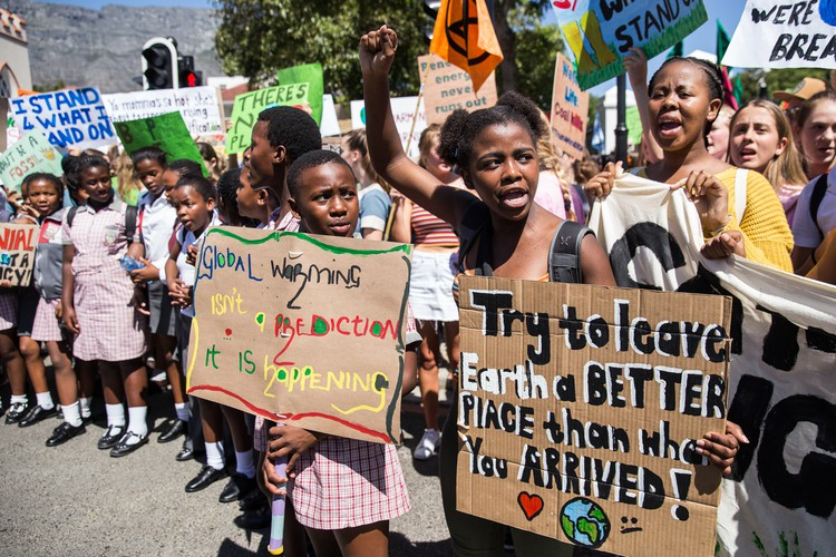 Grade 11 pupil Zenile Ngcame of Masiphumelele High School, raises her fist during a protest for climate change outside Parliament in Cape Town.