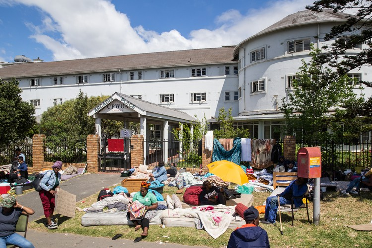 Photo of building with people\'s beds on the lawn