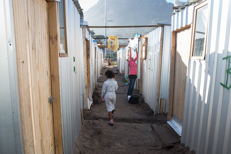 Photo of shacks and a child