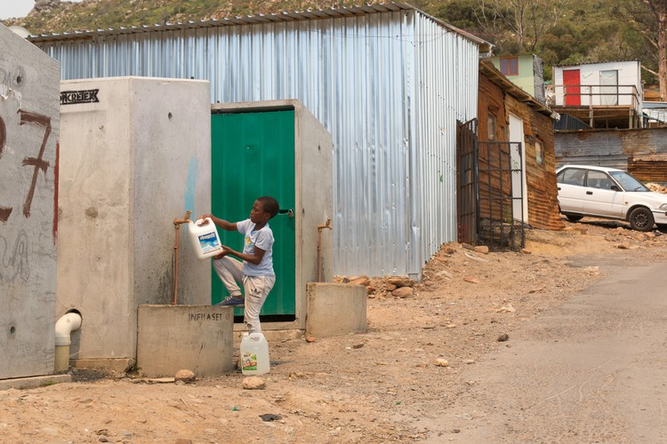 Photo of boy filling a can with water