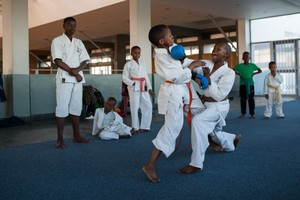 Photo of a young boy practicing karate at a dojo in Khayelitsha