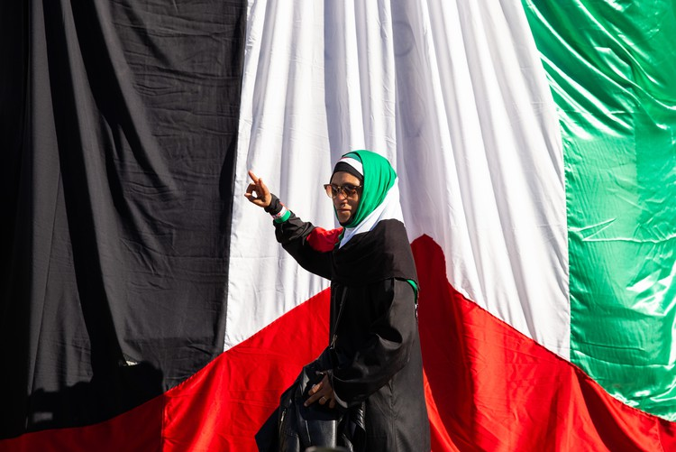 Photo of a woman in front of a large Palestinian flag