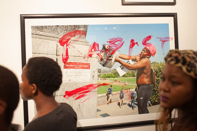 People look at photos in the exhibition, one of which is of Chumani Maxwele