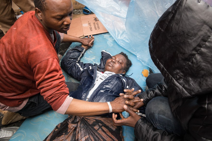 A woman lies on the ground during the eviction. Protesters used a plastic sheet to protect her from the water being sprayed by the police water cannon.