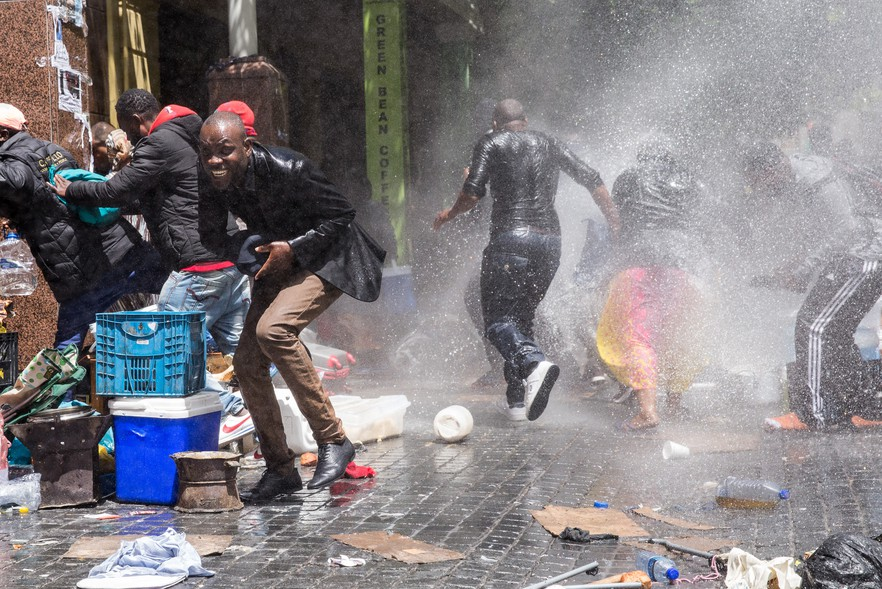 Police use a water cannon to disperse protesters.