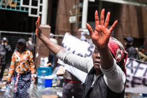 "A women lifts her hands that was dippid in red coloured water which is used by the police water canon. She said that it resembles ""blood""."