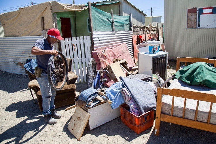 Photo of a man and belongings in the street outside a house
