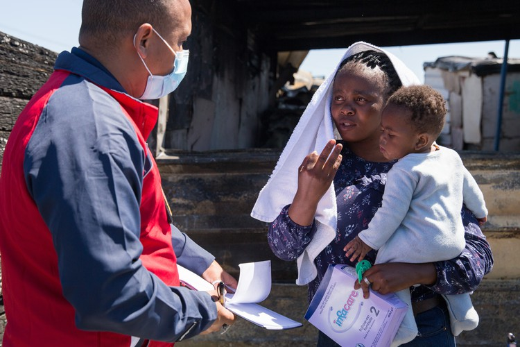 Lona Myeko holds her six-month-old son Melokuhle while speaking to Ashwin Maxim of the City of Cape Town's disaster risk management centre on Thursday. Photo: Ashraf Hendricks