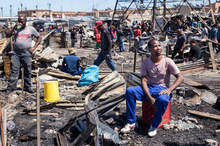 Father of three, Mawethu Nayo (seated on the red crate) was home with two of his children when a fire started in Langa on Thursday morning. He managed to save his children and some clothing. He had just taken his wife to hospital on Wednesday to have their baby. He worries about what they will be returning to. Photo: Ashraf Hendricks