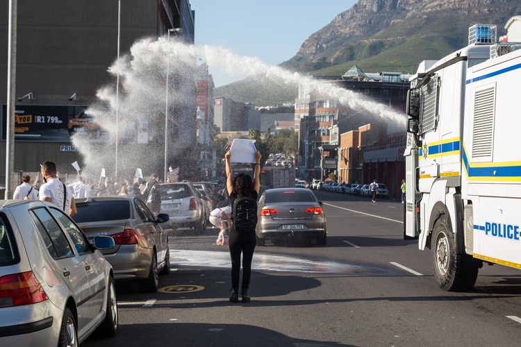 Police disperse demonstrators during a protest against Covid-19 restrictions in the hospitality and tourism industry outside Parliament in Cape Town. - Ashraf Hendricks