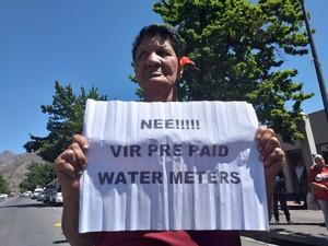 Photo of woman holding placard complaining about water meter