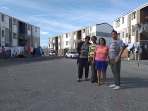 Photo of four people against background of flats