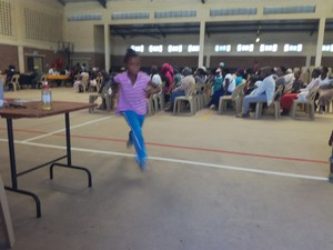 Photo of people in a hall and a child running