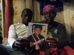 Photo of parents with picture of their child