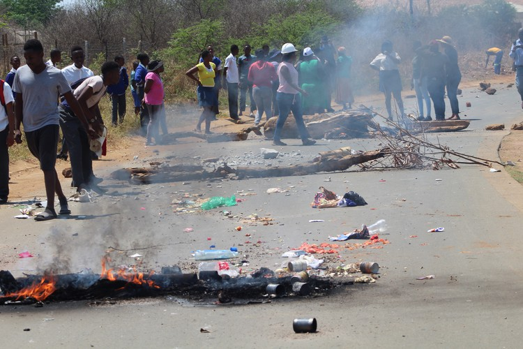 Photo of debris burning on road, with protesters