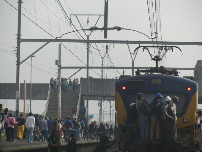 Photo of people hanging onto the back of a train