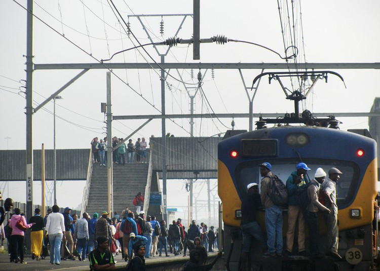 Photo of a train with people clinging to the outside