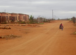 Photo of a dusty street and RDP houses