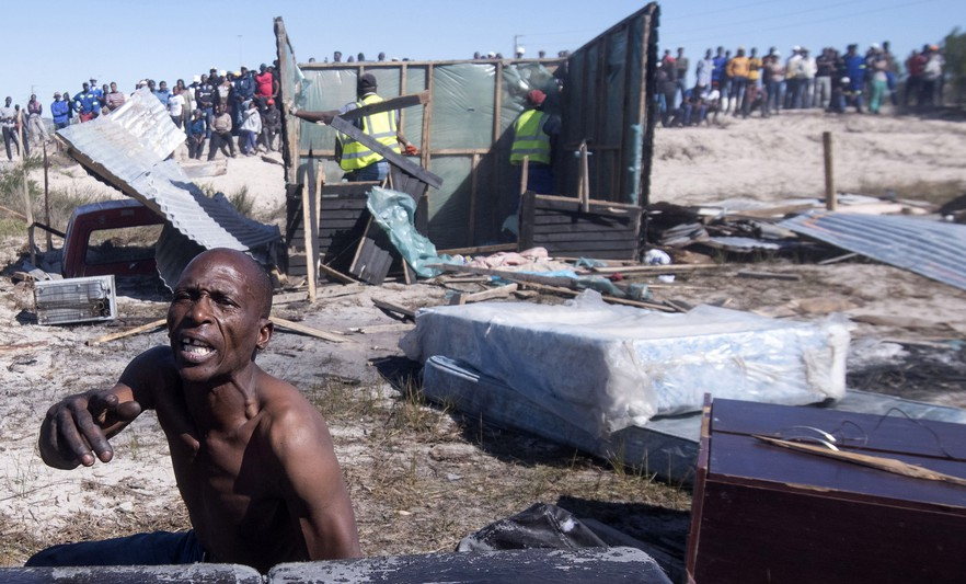 Alex Midikana sits amongst his belongings as shacks are removed. When Law Enforcement arrived yesterday, Midikana's home was spared. Today it too was removed. Photo: Brenton Geach