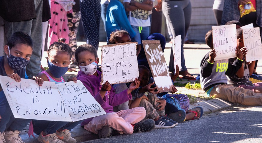 Photo of children sitting holding placards