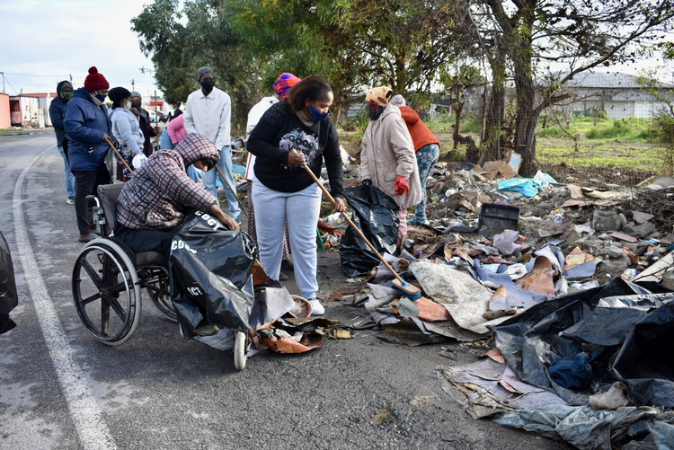 Photo of people, one in a wheelchair, cleaning up rubbish