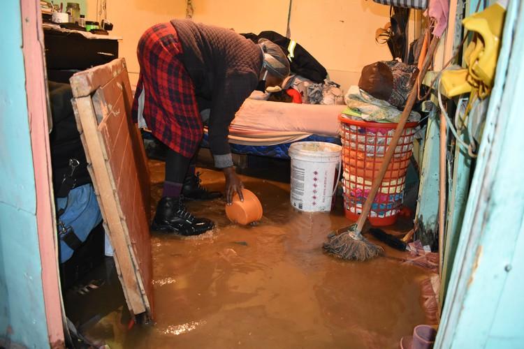 Ntombizodwa Duba from Khunqu informal settlement in Khayelitsha scoops water out of her shack. Photo: Buziwe Nocuze