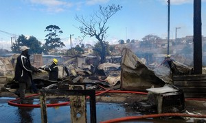 Photo of firefighters and burnt shacks