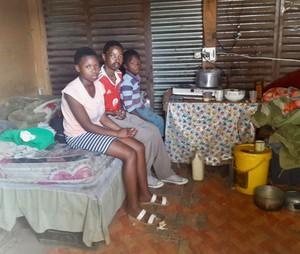 Photo of three people sitting on a bed in a shack