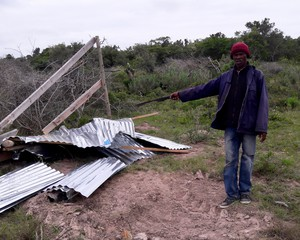 Photo of a man and a demolished shack