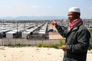 Photo of a man pointing to rows of zinc houses