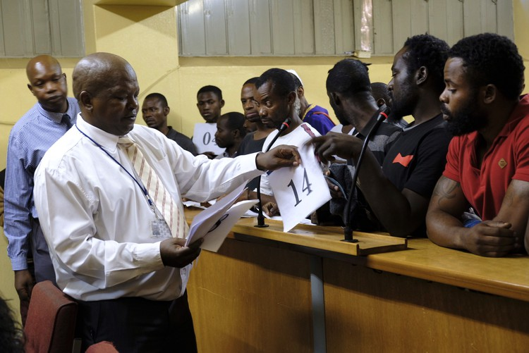Photo of man handing out numbers in court